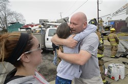 Bryan Hutchens, right, the owner of Hutch's Diner in Butler who was working in the building on Center Avenue at the time the fire started, is hugged on Sunday by Aylssia Mazzanti, a family friend, as firefighters continue to quench flames at the site.