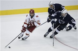 Denver's Troy Terry looks to pass as Penn State's Dylan Richard (12) and Liam Folkes give chase in the second period Sunday in Cincinnati.