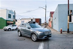 Operators ride inside one of Uber's self-driving SUVs along Penn Avenue in the Strip District.