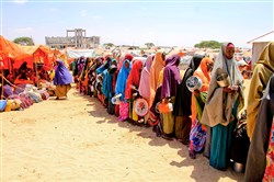 Displaced Somali women stand in a queue Monday to receive food handouts in a camp just outside of Mogadishu in Somalia. Somalia's drought is threatening 3 million lives, according to the U.N. In recent months, aid agencies have been increasing their efforts, but they say more support is needed to prevent the crisis from worsening.