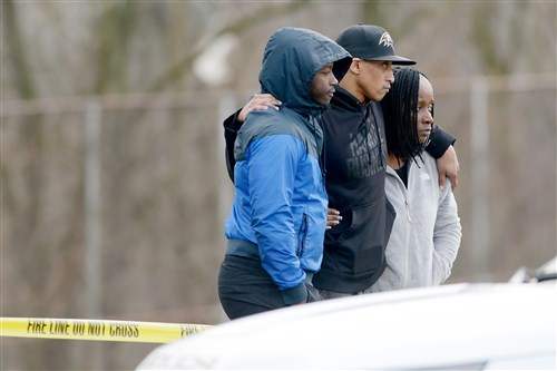 People watch as Penn Hills and Allegheny County Police investigate the shooting death of a teenager Tuesday at the Linton Middle School playground in Penn Hills.