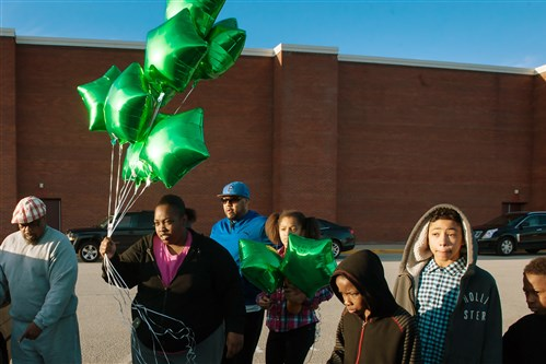 Cynthia Marshman, 27, carries balloons to the parking space where her nephew, 16-year-old Deven Holloway, was shot and killed outside of Linton Middle School after a vigil for Deven Wednesday at the school in Penn Hills.