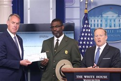 White House press secretary Sean Spicer gave Interior Secretary Ryan Zinke, left, the first quarter check of President Donald Trump's salary which he donated to the National Park Service as Tyrone Brandyburg, Harpers Ferry National Historical Park Superindendant, looks on during the daily press briefing at the White House on April 3, 2017.