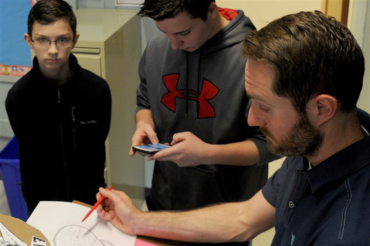 20170316lf-Avonworth02-1 Avonworth eighth-graders, left to right, Brooke Johncour, Eli King and Sean McAleer work with teacher Jason Smith on the Chase the Antelopes 5K Run project.