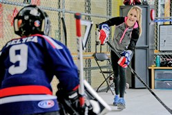 Former Robert Morris and U.S. Olympic goalie Brianne McLaughlin practices with Carson Relyea, 8, of Moon Township during a private lesson at RMU Island Sports Center in Neville Island on April 4.