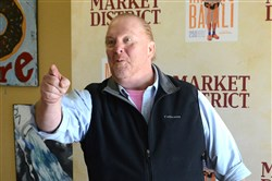 Mario Batali arrived at the Giant Eagle Market District in Robinson in his signature outfit: a black vest over a shirt with rolled-up sleeves, Bermuda shorts, blue socks and orange Crocs.