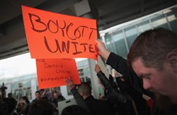 Demonstrators protest outside the United Airlines terminal at O'Hare International Airport in Chicago on Tuesday.