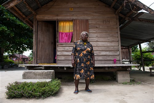 Georga Burger stands for a portrait outside of the one room house in New Ganze, Suriname that she was relocated to when her village was flooded to provide water for the Afobaka Dam.