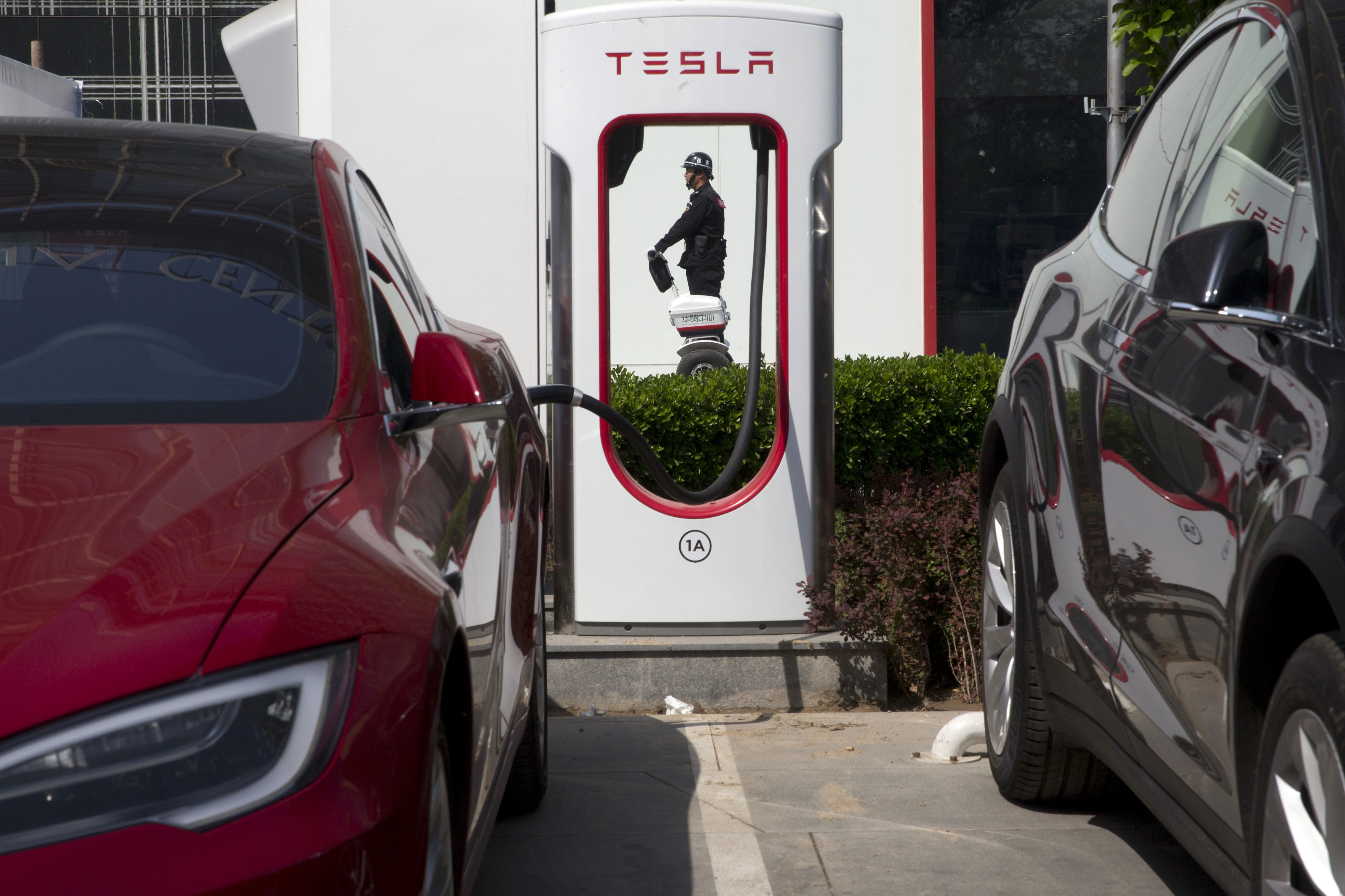 China Electric Car Dreams-1 In this Friday, April 14, 2017 photo, a security personnel riding a motorized platform moves past an electric vehicle charging station in Beijing, China. Automakers face a conflict in China's huge but crowded market: Regulators are pushing them to sell electric cars, but buyers want gasoline-hungry SUVs. (AP Photo/Ng Han Guan)