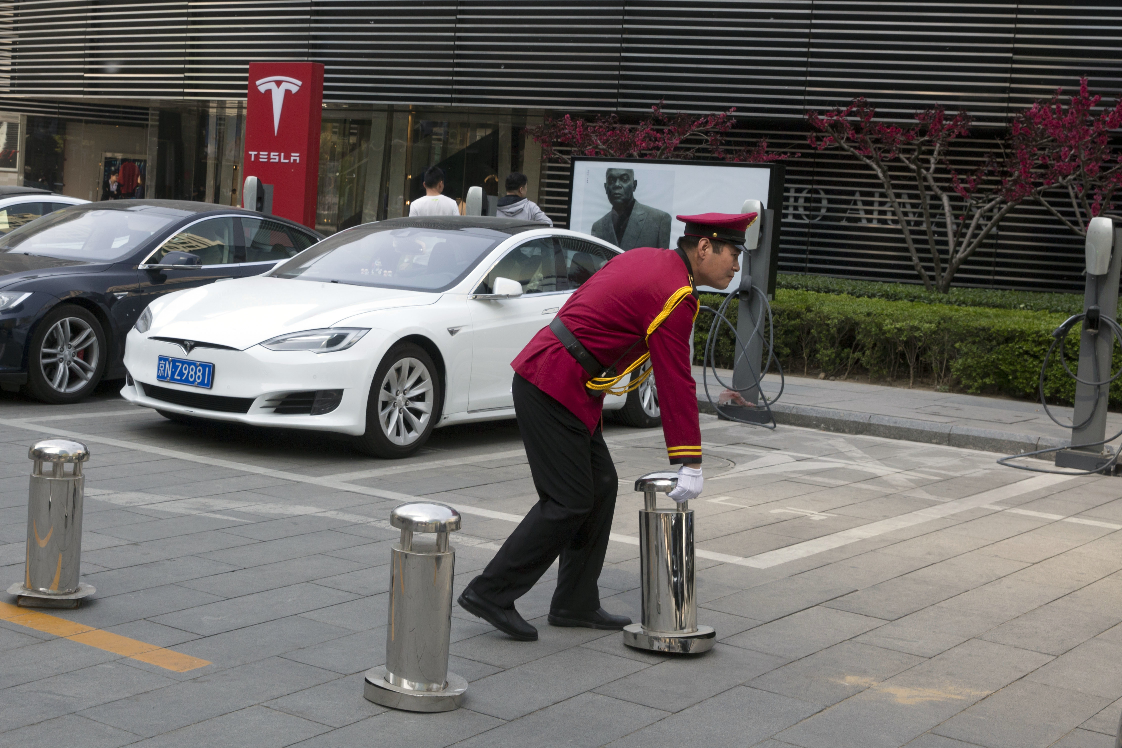 China Electric Car Dreams-2 In this Friday, April 14, 2017 photo, a security personnel removes barricade near an area closed off for Tesla electric vehicles to charge in Beijing, China. Automakers face a conflict in China's huge but crowded market: Regulators are pushing them to sell electric cars, but buyers want gasoline-hungry SUVs. (AP Photo/Ng Han Guan)