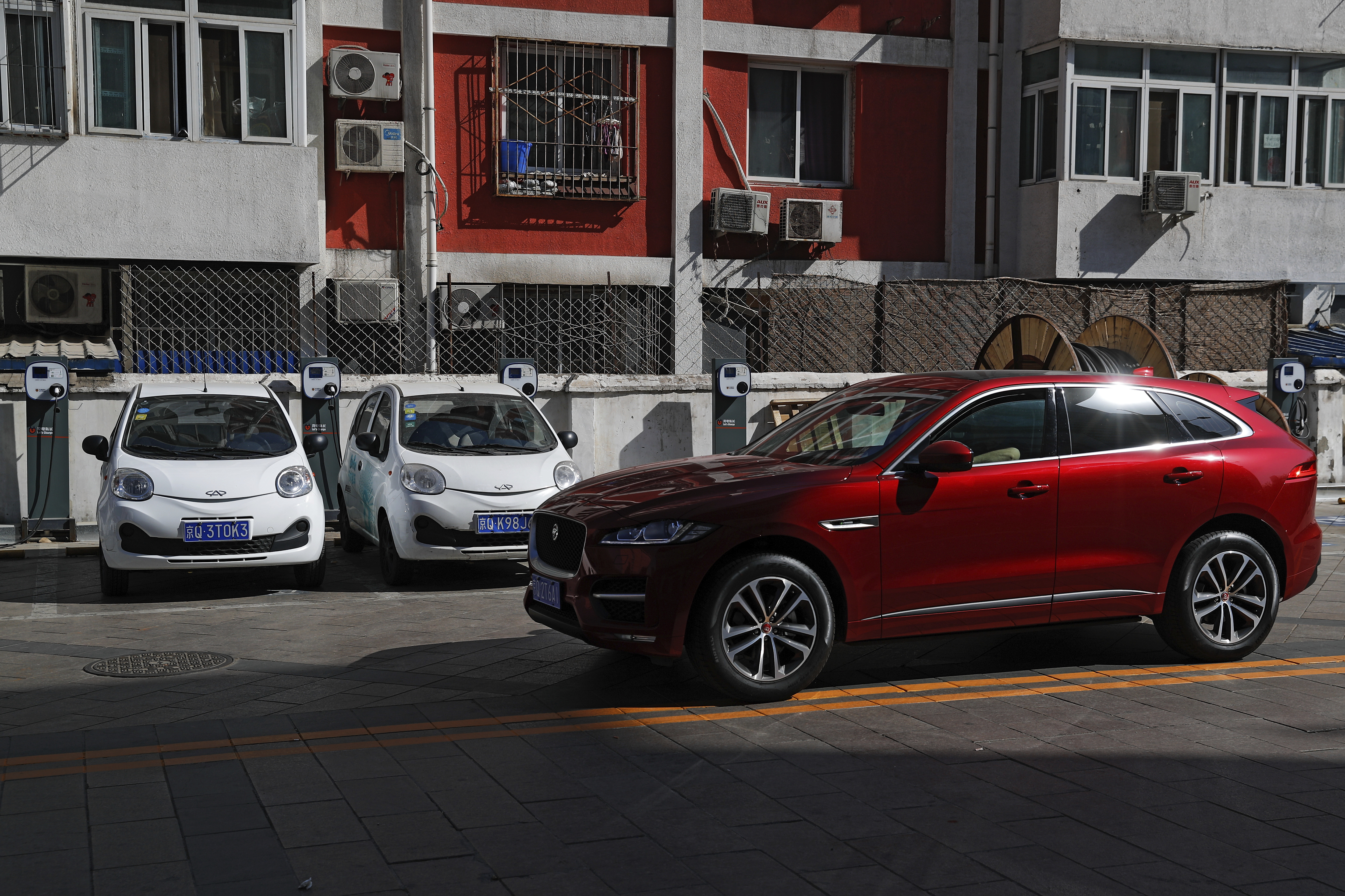 China Electric Car Dreams-3 In this Friday, April 14, 2017 photo, a SUV vehicle drives past electric cars parked at a charging station outside a residential building in Beijing. Automakers face a dilemma in China, where regulators are pressing them to sell electric cars but consumers want gas-guzzling SUVs. This month's Shanghai auto show, the industry's biggest marketing event of the year, will showcase efforts to create electric models Chinese drivers want to buy. (AP Photo/Andy Wong)