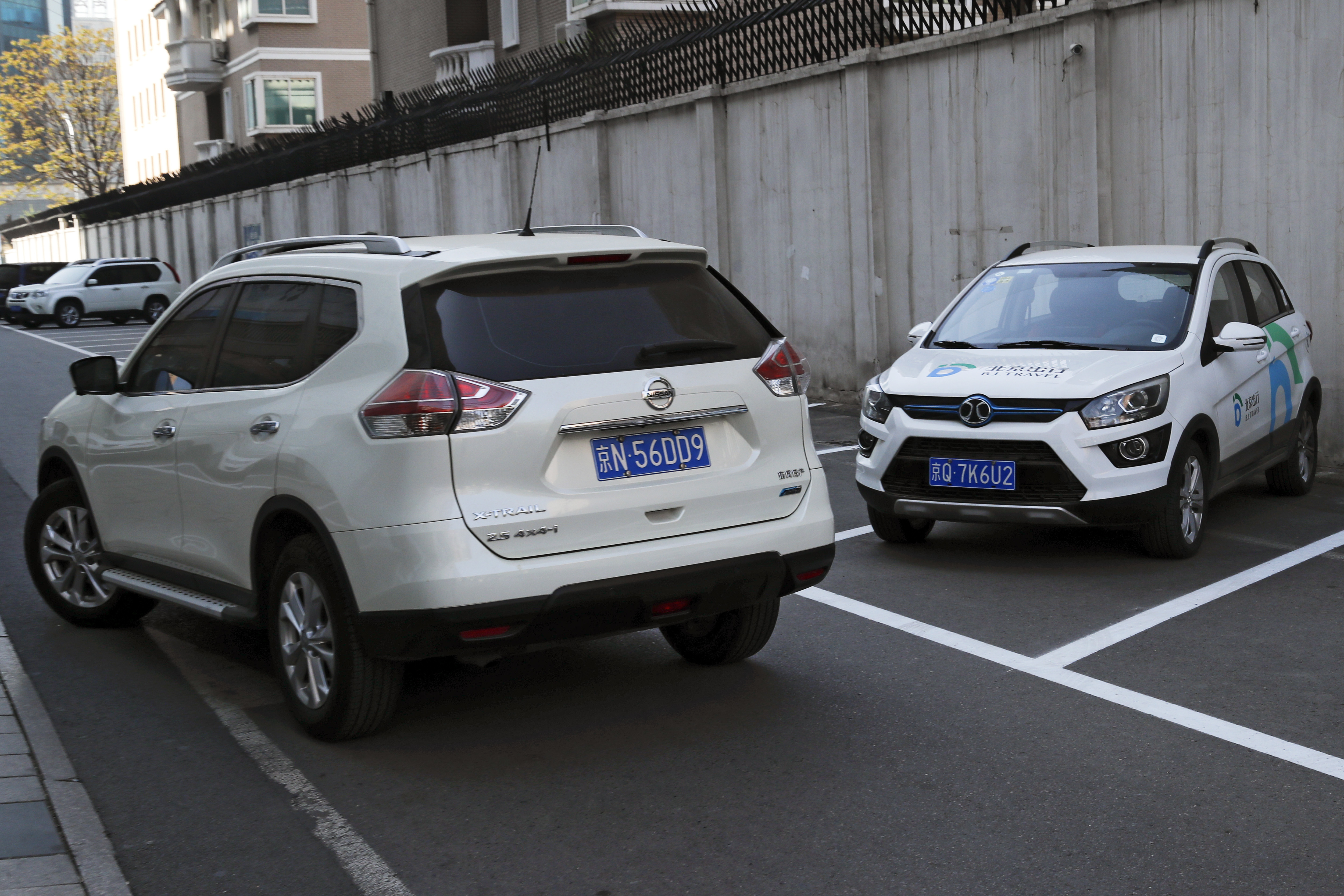 China Electric Car Dreams-4 In this Friday, April 14, 2017 photo, a SUV vehicle, left, drives past an electric-powered SUV parked outside a shopping mall in Beijing. Automakers face a dilemma in China's huge but crowded market: Regulators are pushing them to sell electric cars, but buyers want gas-guzzling SUVs. This month's Shanghai auto show, the industry's biggest marketing event of the year, will showcase efforts to create electric models Chinese drivers want to buy. (AP Photo/Andy Wong)
