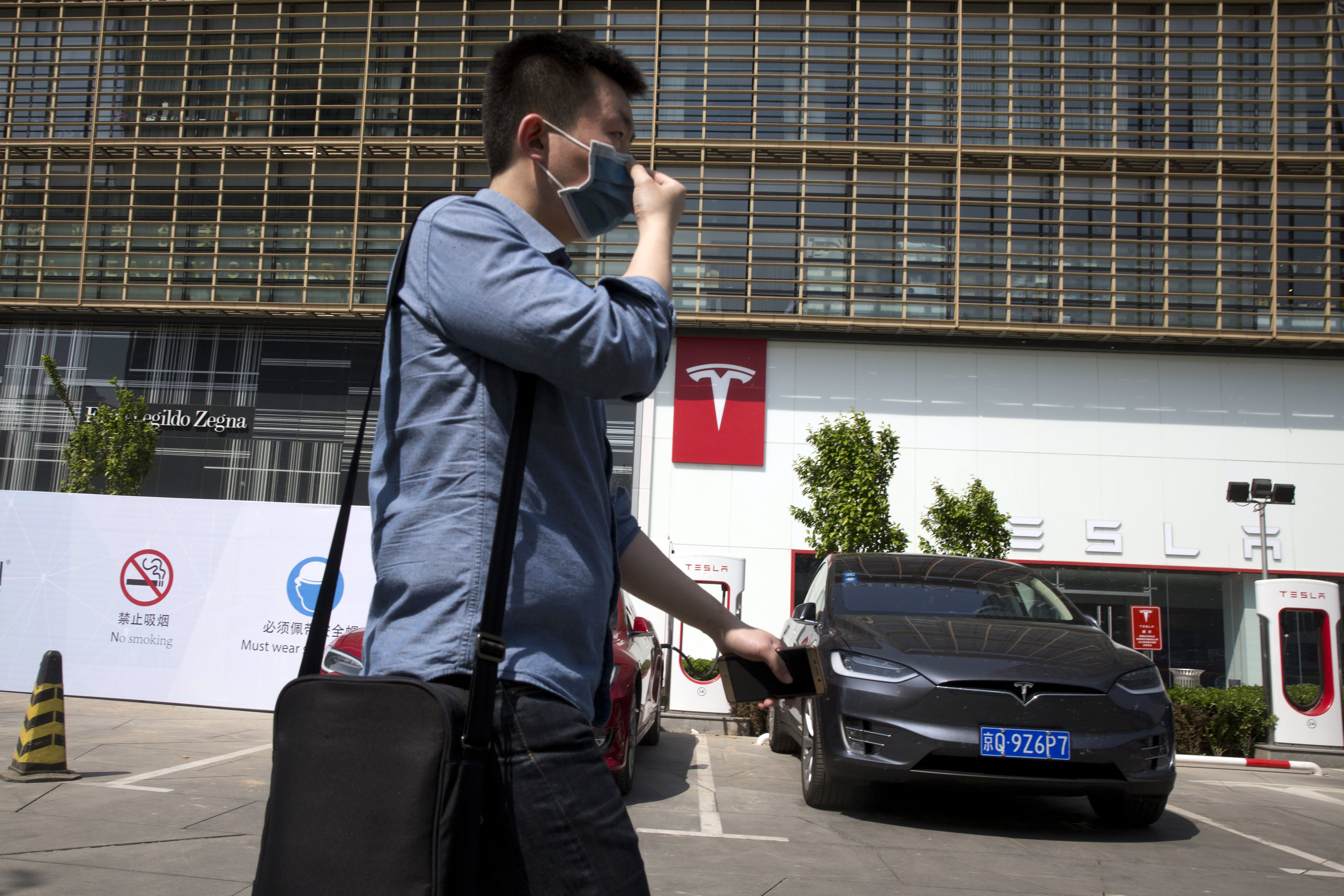 China Electric Car Dreams In this Friday, April 14, 2017 photo, a man wears a mask walks past a Tesla electric vehicle showroom and charging station in Beijing, China. Automakers face a conflict in China's huge but crowded market: Regulators are pushing them to sell electric cars, but buyers want gasoline-hungry SUVs. (AP Photo/Ng Han Guan)