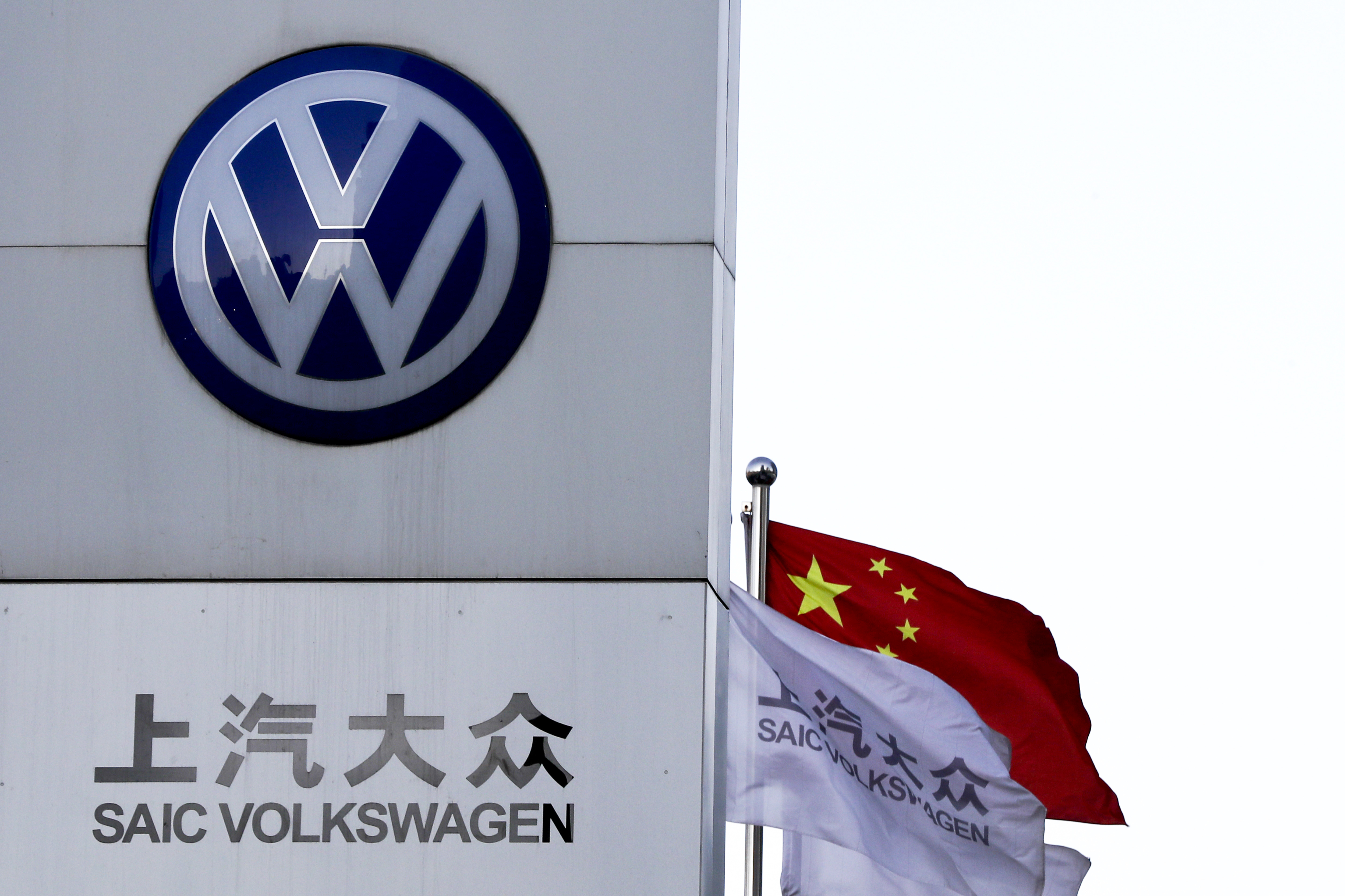 China Auto Show-9 A Chinese national flag flutters near a SAIC Volkswagen, a joint venture between SAIC Motor and Volkswagen's dealer showroom and service center in Beijing, Tuesday, April 18, 2017. Volkswagen, Europe's biggest automaker, plans to launch its first pure-electric car in China next year as Beijing steps up pressure on the industry to reduce reliance on gasoline, following the announcement Tuesday comes on the eve of the Shanghai auto show, which showcases industry efforts to create electric cars with consumer appeal. (AP Photo/Andy Wong)