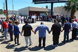 Pastors and church leaders gather for a final prayer following a prayer walk for the victims of Tuesday's triple-homicide near downtown Fresno, Calif., on Thursday.