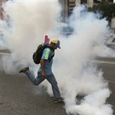 An anti-government protester kicks a tear gas canister during clashes with security forces in Caracas, Venezuela, on Thursday.