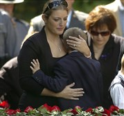 In this Sept 18, 2014, file photo, Tiffany Dickson embraces her son Bryon III, in front of the casket of her husband Pennsylvania State Trooper Cpl. Bryon Dickson at the Dunmore Cemetery in Dunmore, Pa.