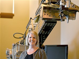 """Rebecca Hartley, director of operations for the Clemson University Center for Workforce Development and chief workforce officer for the Advanced Robotics in Manufacturing Institute, stands in front of the """"Workhorse,"""" one of the first robots built by the institute designed to clean-up contaminated sites."""