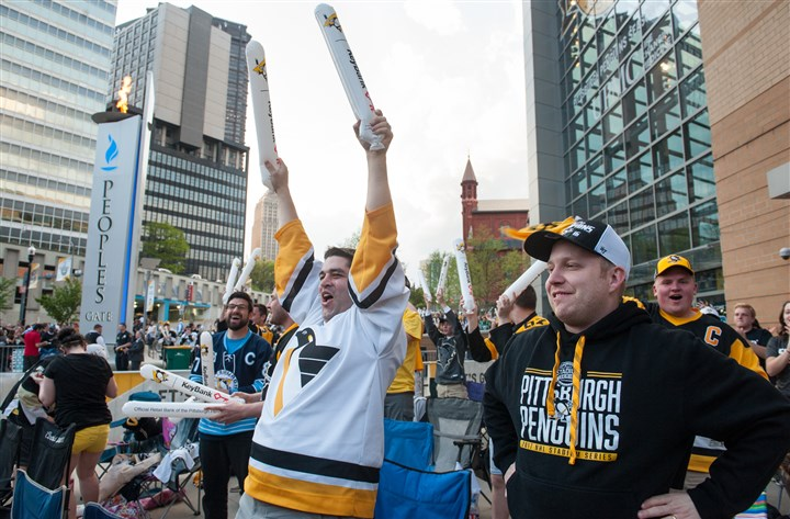 20170420smsPens07-1 Bill Garrard, center, of Friendship watches the Penguins score in Game 5 Thursday at the team's watch party outside PPG Paints Arena.