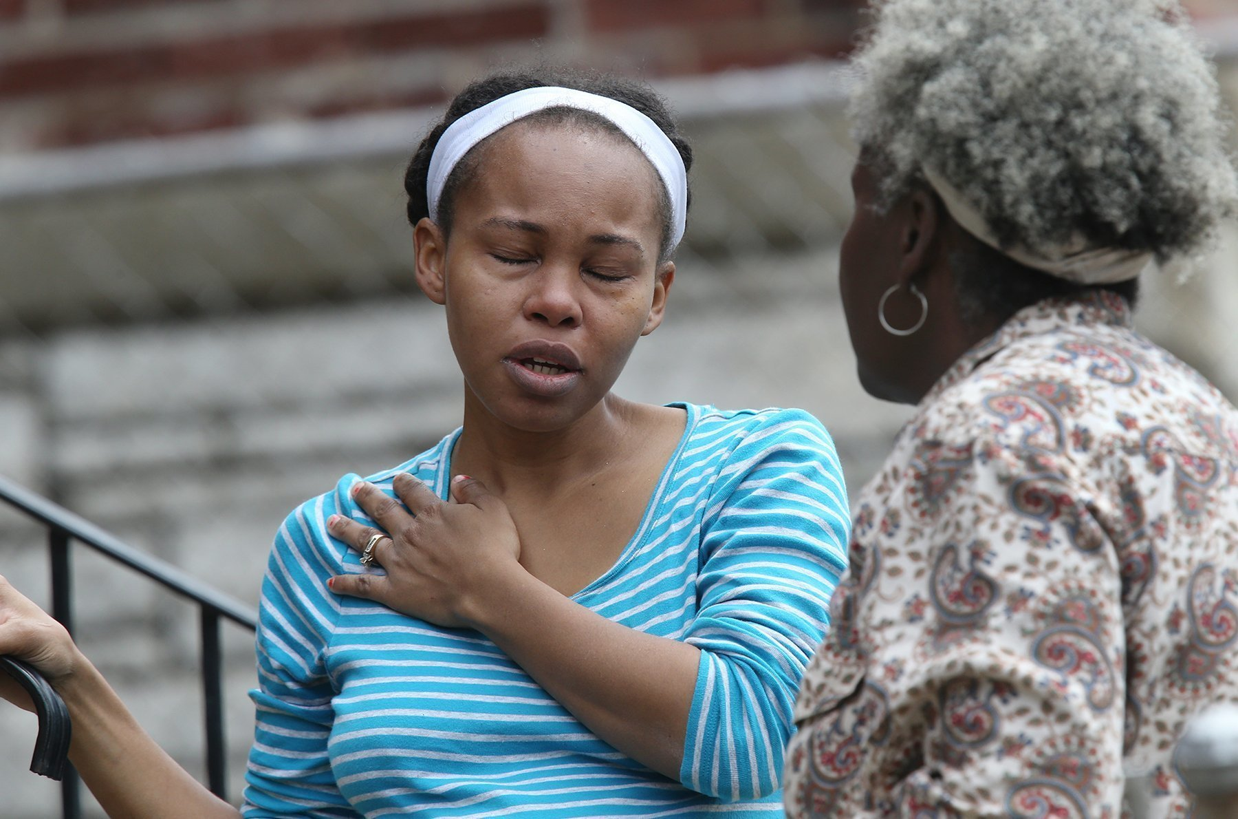 CORRECTION Utility Workers Killed-2 CORRECTS FIRST NAME TO MANYIKA Manyika McCoy, left, cries while she talks to her mother Alice Spann, Thursday, April 20, 2017, in St. Louis. McCoy had just been talking to two Laclede Gas Co. workers just before they were killed by a man who walked up and started shooting. (J.B. Forbes/St. Louis Post-Dispatch via AP)