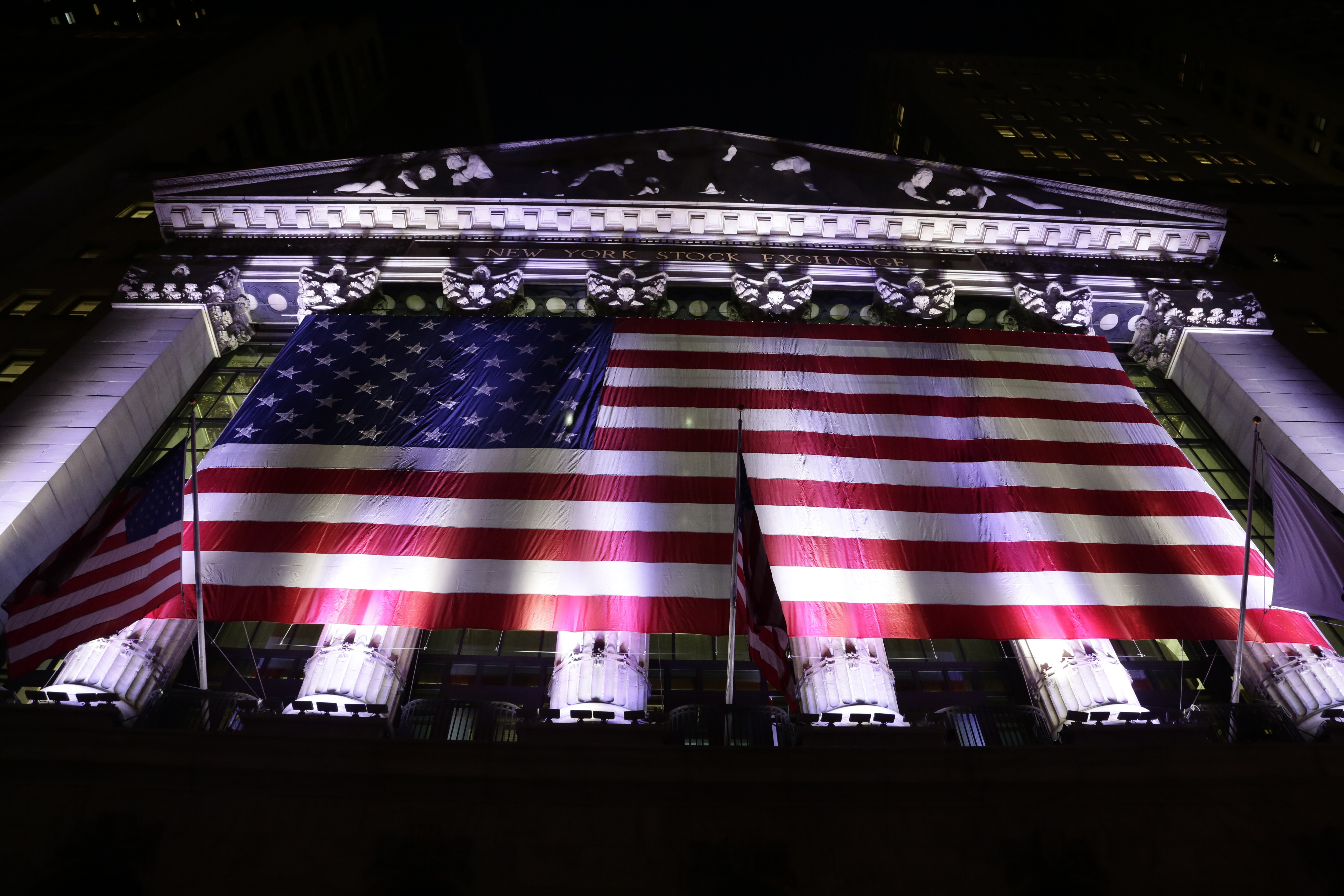 Financial Markets Wall Street In this evening Friday, Feb. 17, 2017, photo, an American flag hangs on the front of the New York Stock Exchange. European stocks declined while most Asian markets rose Friday, April 21, 2017, ahead of the first round of voting in France's closely watched presidential election. (AP Photo/Peter Morgan)