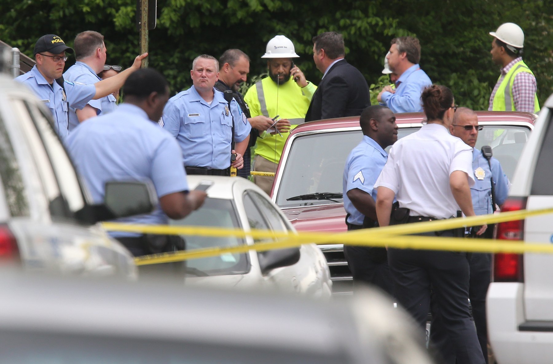 Utility Workers Killed-1 St. Louis police and Laclede Gas Co. workers congregate after a fatal shooting Thursday, April 20, 2017, in St. Louis. Manyika McCoy had just been talking to two Laclede Gas Co. workers just before they were killed by a man who walked up and started shooting. (J.B. Forbes/St. Louis Post-Dispatch via AP)