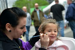 Parker Sommer, 3, from Downtown, has her face painted by Alyssa Smart from Beaver with Face Paint Pittsburgh at the Paint the Square Green Earth Day event Saturday.