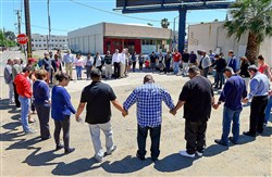Pastors and church leaders gather Thursday for a final prayer following a prayer walk for the victims of Tuesday's triple-homicide near downtown Fresno, Calif. Members of the Pastor Clusters of the Fresno/Clovis area traced the route of the alleged killer, holding prayers at the location of each victim.