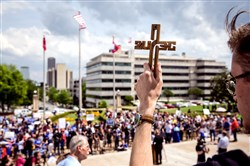 Austin Gurchiek holds up a cross as he and other demonstrators gather April 14 in front of the Arkansas State Capitol building to protest the death penalty and the state's plans to carry out seven executions in 10 days, in Little Rock, Ark.