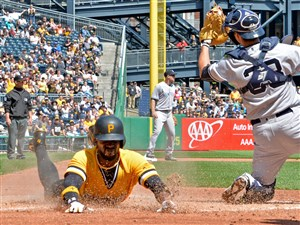 The Pirates' Andrew McCutchen scores on a double by Gregory Polanco against the Yankees in the third inning.