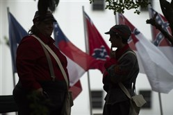 People dressed in Confederate Army clothing stand outside the Alabama Capitol building during a rally around the Confederate Monument on Confederate Memorial Day Monday in Montgomery.