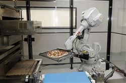 In this Aug. 29, 2016 photo, a robot places a pizza into an oven at Zume Pizza in Mountain View, Calif. Zume is one of a growing number of food-tech firms seeking to disrupt the restaurant industry with software and robots that they say let them cut costs, speed production and improve worker safety.