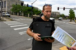 Jason Jablon hands out fliers Thursday morning at the intersection of Butler Street and 40th Street in Lawrenceville.