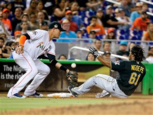 Gift Ngoepe slides in safely to third for a triple ahead of the throw to Marlins third baseman Martin Prado.