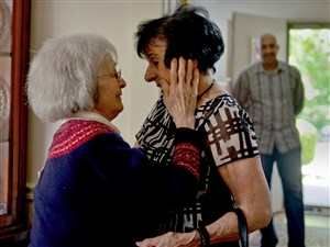 Therese Rocco, left, embraces Leila McClain while Ms. McClain's son, Sam, looks on during their reunion.