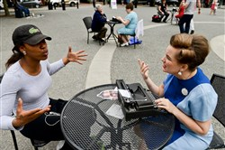 """De'Asha Mitchell, 20, of the South Side dictates her letter to Patricia Good during the """"I Wish To Say"""" public art performance by artist Sheryl Oring on Friday in Market Square, Downtown."""