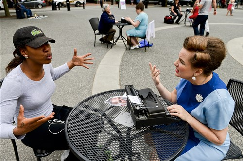 "De'Asha Mitchell, 20, of the South Side dictates her letter to Patricia Good during the ""I Wish To Say"" public art performance by artist Sheryl Oring on Friday in Market Square, Downtown."
