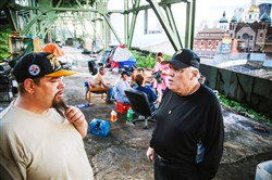 Jack Brumbaugh, right, with Blankets Over Pittsburgh talks to John Flint, who lives in a tent camp under a bridge on the South Side.