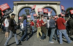 In this Dec. 13, 2007, file photo, striking writers walk the picket line outside Paramount Studiosin Los Angeles.
