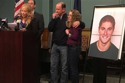 A picture of Timothy Piazza, 19, of Lebanon, N.J., stands next to his parents during a press conference in Bellefonte, Pa., announcing charges against 18 members of the now-shuttered Beta Theta Pi fraternity and the frat itself, in connection with Piazza's death.