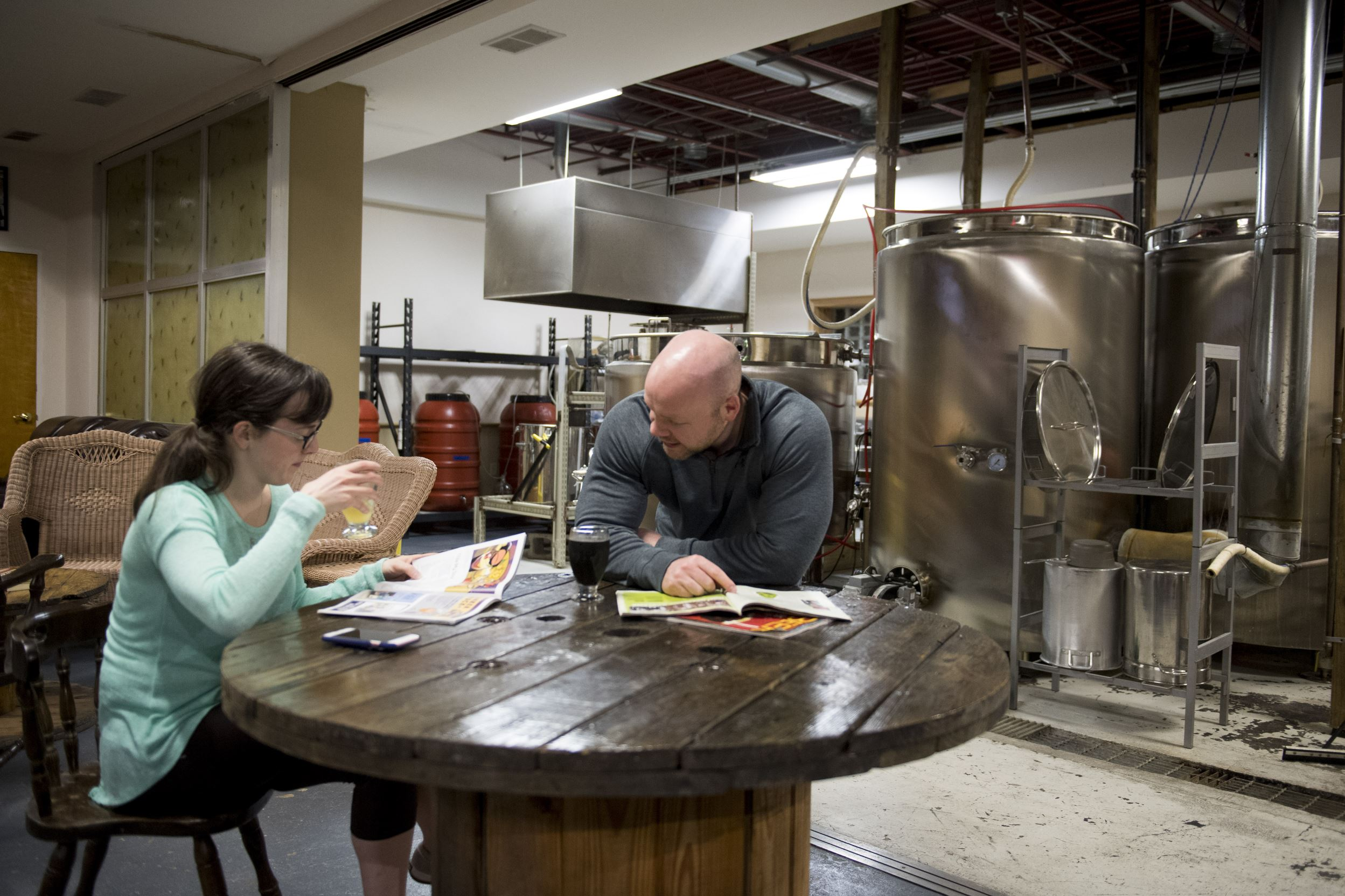 20170505scPetrucci-04-9 Andy Forrest of Center Township and Katy Hiser of Ellwood City read magazines while enjoying beer on Friday, May 5, 2017 at Petrucci Brothers Brewing in New Brighton.