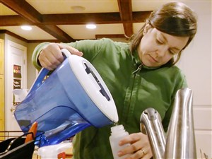 Casey Mednis fills a bottle of water to test lead levels in the kitchen of her Regent Square home.