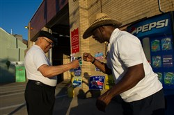 Raymond Peters, left, arrives to vote and is greeted by  Rev. Michael Murray, 15th Ward secretary and temporary constable, at Engine Company 13 in Hazelwood.