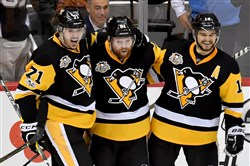 Penguins Phil Kessel is congratulated by Evgeni Malkin and Chris Kunitz after scoring against the Senators in Game 2.
