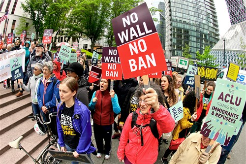 Protesters wave signs and chant during a demonstration against President Donald Trump's revised travel ban on May 15 outside a federal courthouse in Seattle.