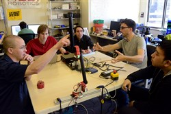 From left, Dave Rollinson, Matthew Tesch, Howie Choset, Curtis Layton and Hoon Ki Kim discuss a development of a robot arm at HEBI Robotics in May in Bloomfield.