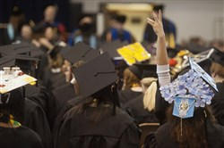 A graduate waves to people in the audience at the commencement ceremony at Clarion University on May 13, 2017