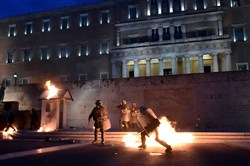 Molotov cocktails are thrown toward police officers in riot gear standing in front of the Greek Parliament in Athens during a rally Thursday against new austerity measures. Protesters took to the streets for a second day, hours before lawmakers voted in Parliament on measures that will impose additional income losses for many Greeks for another three years.