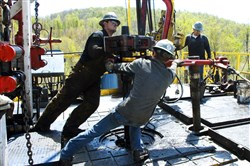 In this April 2010 photo, workers move a section of well casing into place at a Chesapeake Energy natural gas well site near Burlington, Pa., in Bradford County.