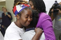 Santcha Etienne hugs a 10-year-old girl who was afraid to have her name used and her face shown after speaking to the media about the Temporary Protected Status for Haitians, because her family is living under the protected status in the Little Haiti neighborhood, on Monday in Miami.